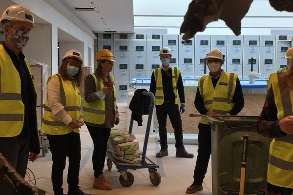 Photo of 6 people in high-vis jackets, helmets and face masks in the Biochemistry building