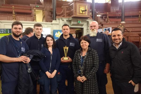 Photo of seven members of DLO staff posing in the Sheldonian Theatre with apprenticeship award