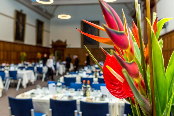 Landscape photo of a large room set up for a formal dinner with bright tropical flower in the foreground